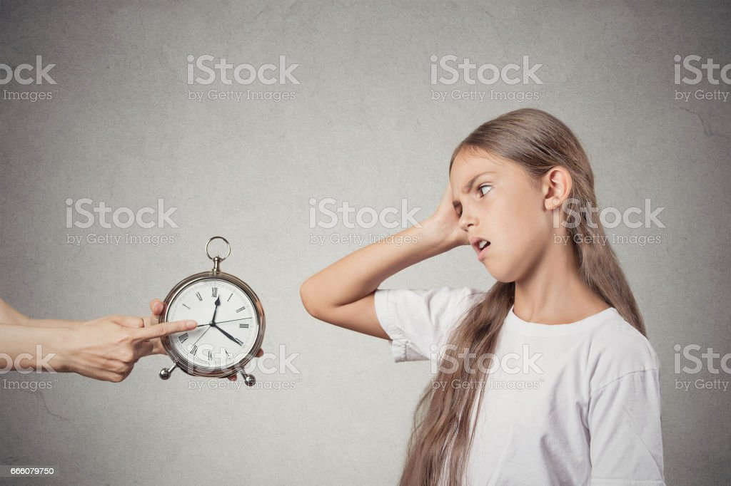 mom showing daughter clock that it is late stock photo