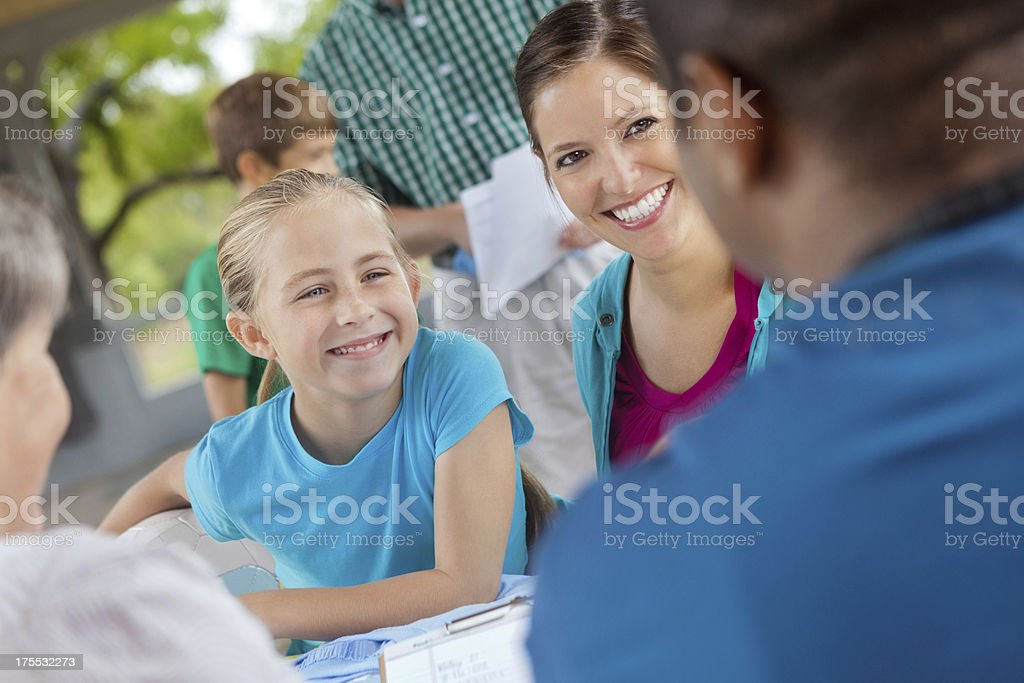 Mom signing daughter up to play sports on soccer team stock photo