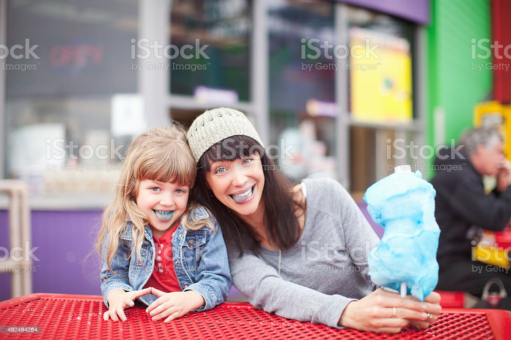 Mom Sitting with Daughter on Beach Boardwalk stock photo