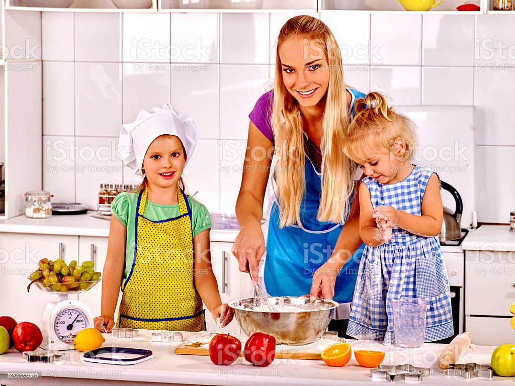 Mom teaches kids to cook in the kitchen stock photo