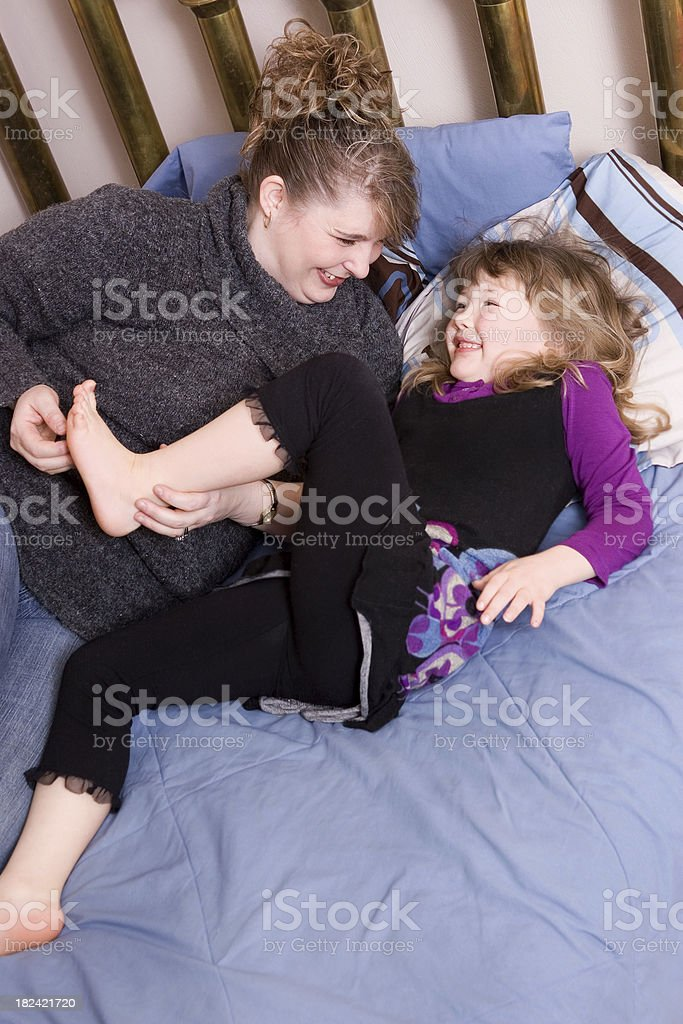 Mom tickling daughter's feet stock photo
