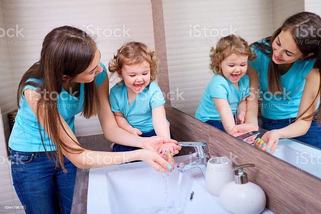 Mom washing baby hands. stock photo