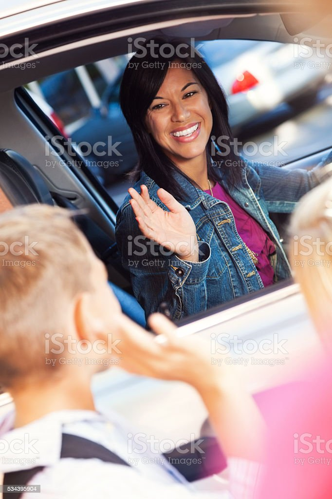 Mom waves at son at drop off at elementary school stock photo