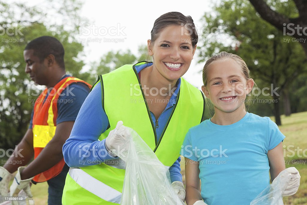 Mom with daughter cleaning up city park/ environmentalism royalty-free stock photo