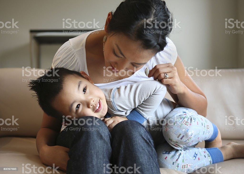 Mom with son on living room couch. stock photo