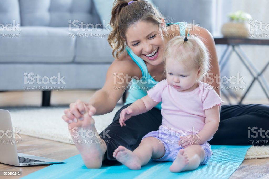 Happy mid adult mom stays fit while working out at home. She is...