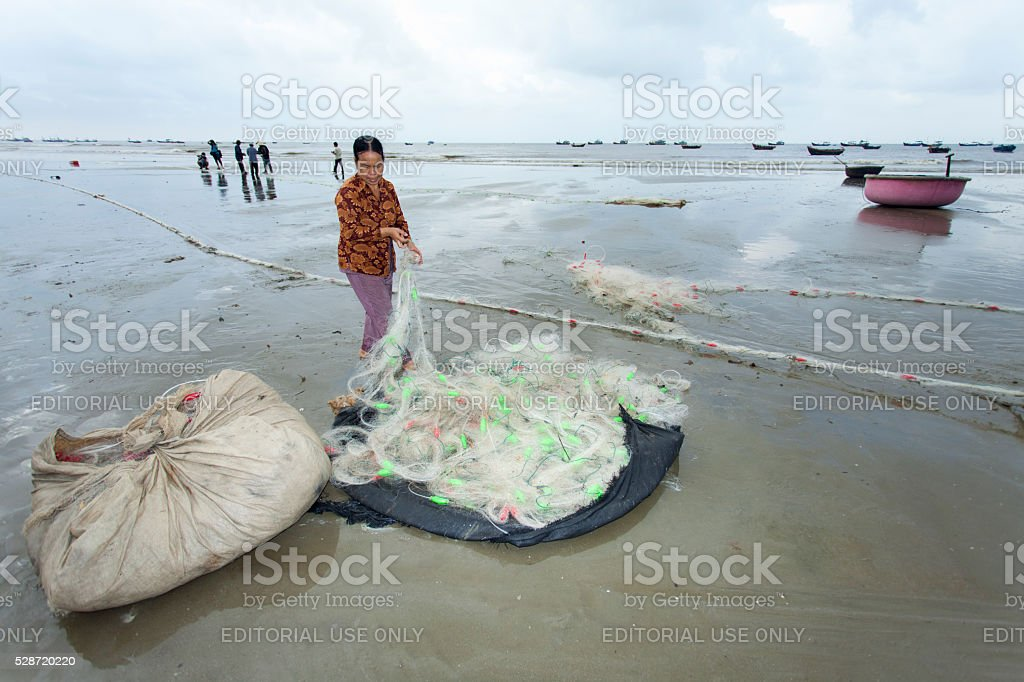 Momen in the Long Hai beach repairing the fishing net stock photo