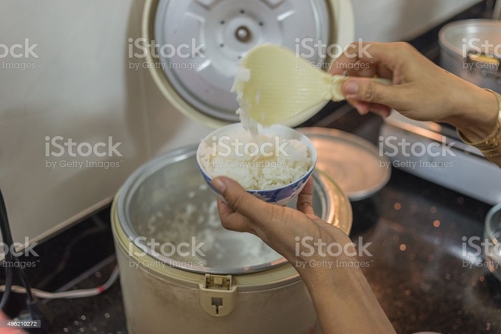 Mommy scooping rice out of rice cooker into small bowl stock photo