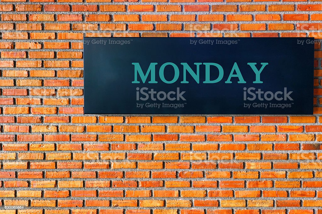 Monday letters on a black background with  brick wall stock photo