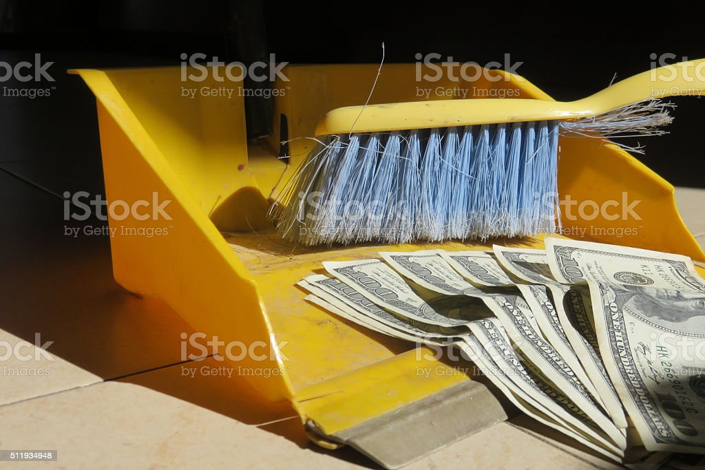 Money and broom stock photo