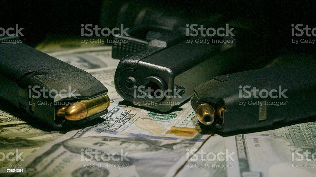 Money and Pistol on One Hundred Dollar Bills stock photo