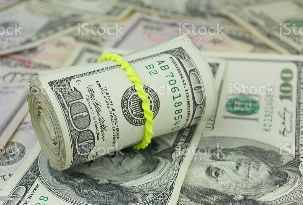 Money background with roll of  american hundred dollar bills stock photo
