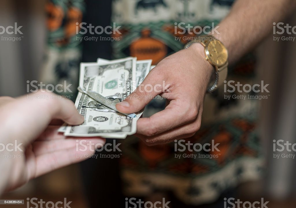 money being exchanged for marijuana joint stock photo