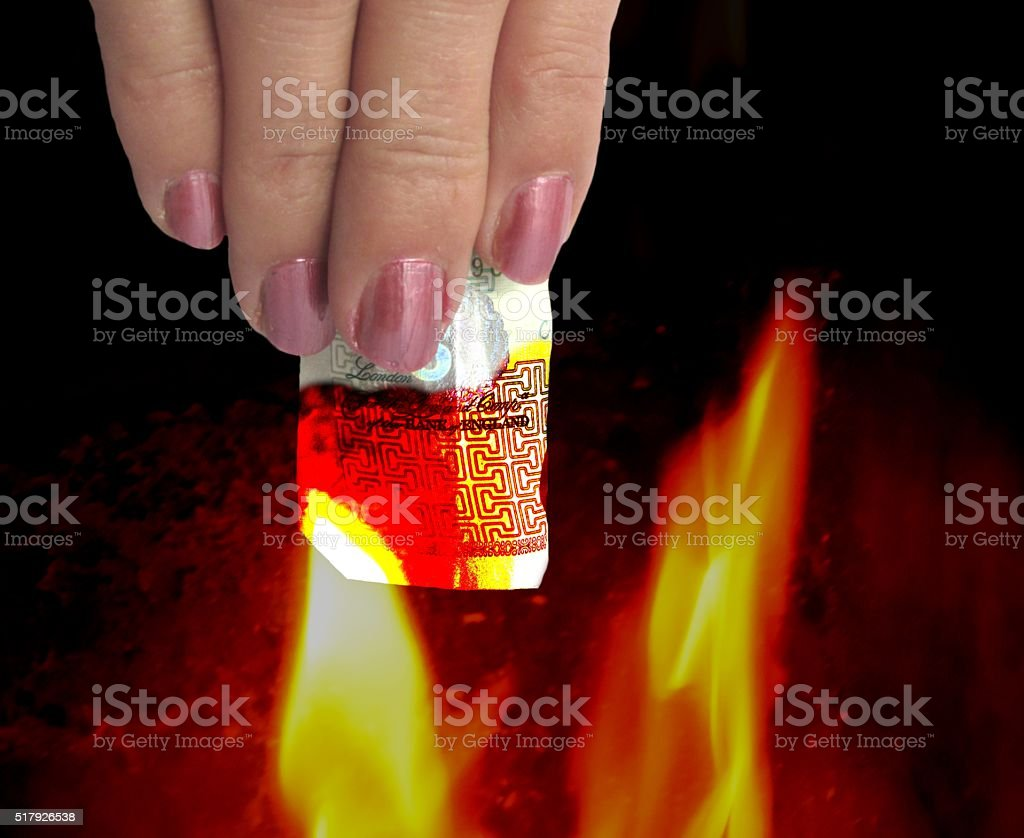 money burning in flames old five pound note stock photo