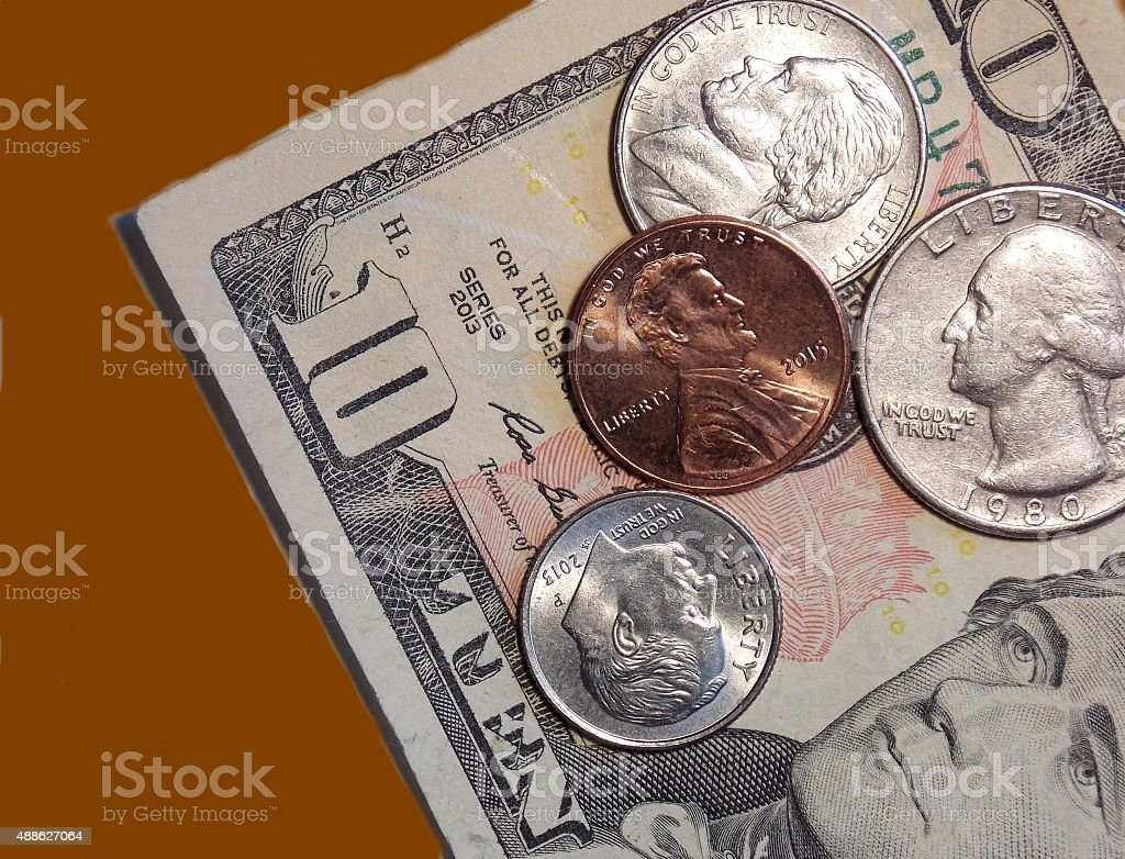 Money - Coins - $10 Bill - Tan Table Background stock photo