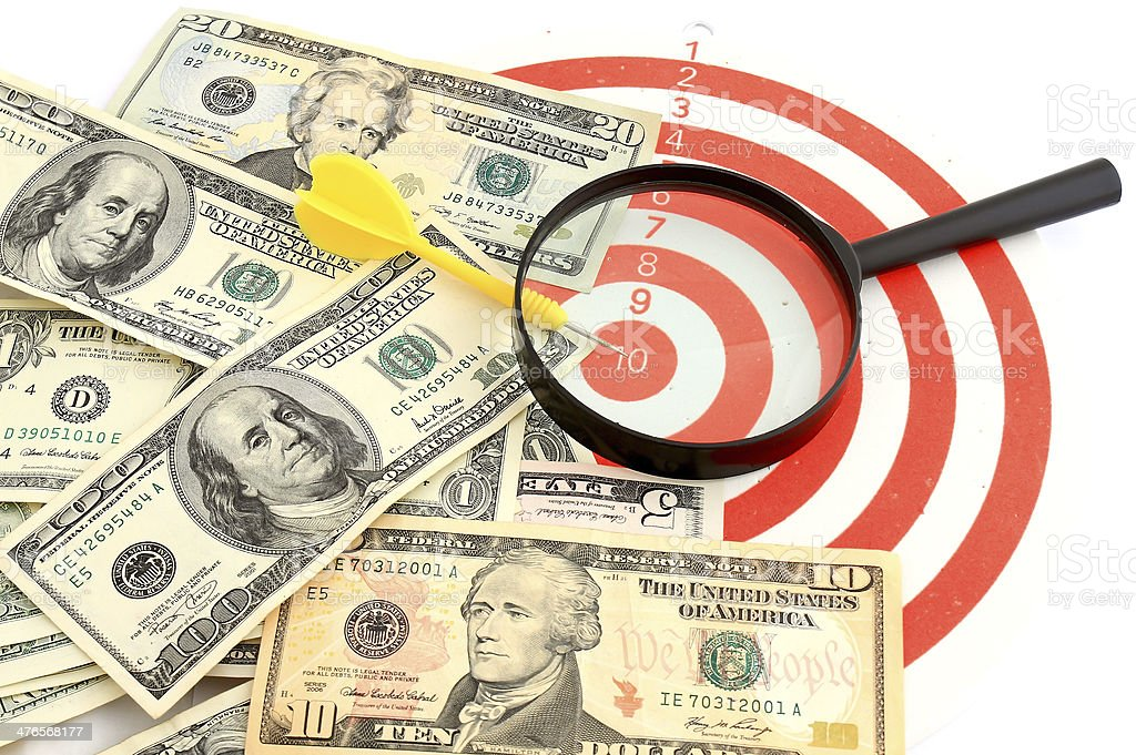 Money dollars and magnifying glass on   darts target royalty-free stock photo