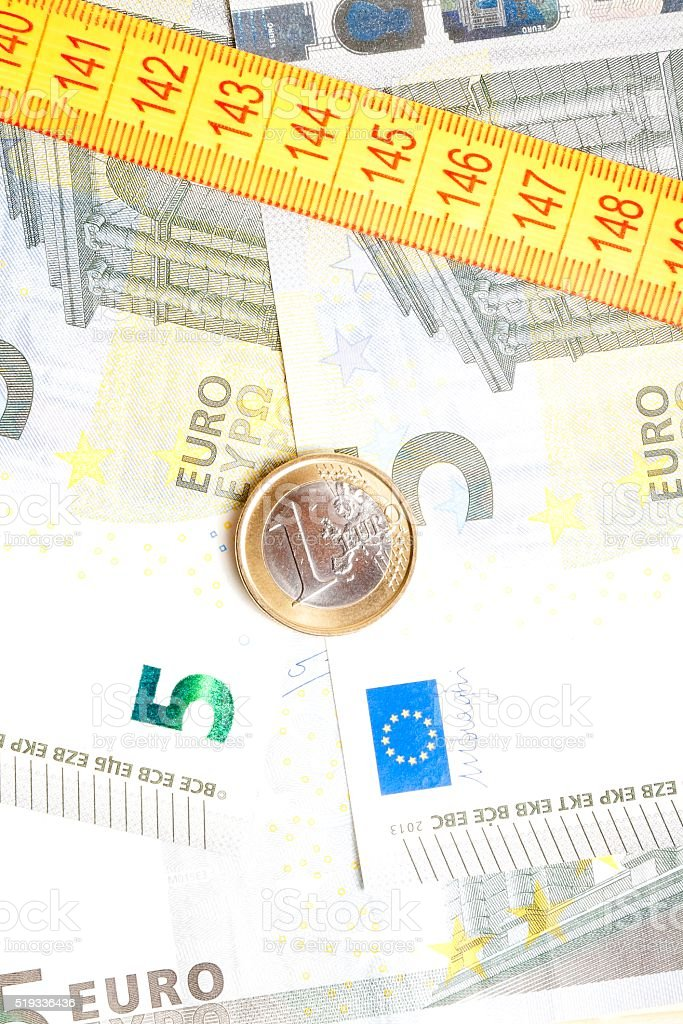 money euro coin on banknotes near measure tape stock photo