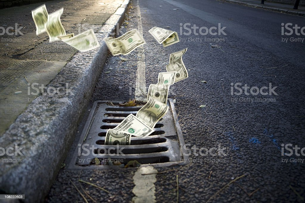 Money falling in a manhole stock photo