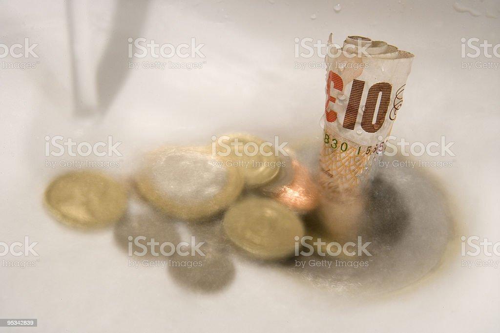 Money going down the drain stock photo