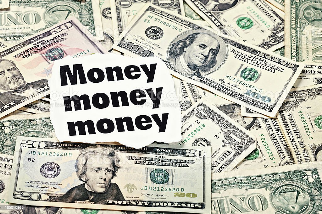 Money headlines backed up by many US dollars royalty-free stock photo