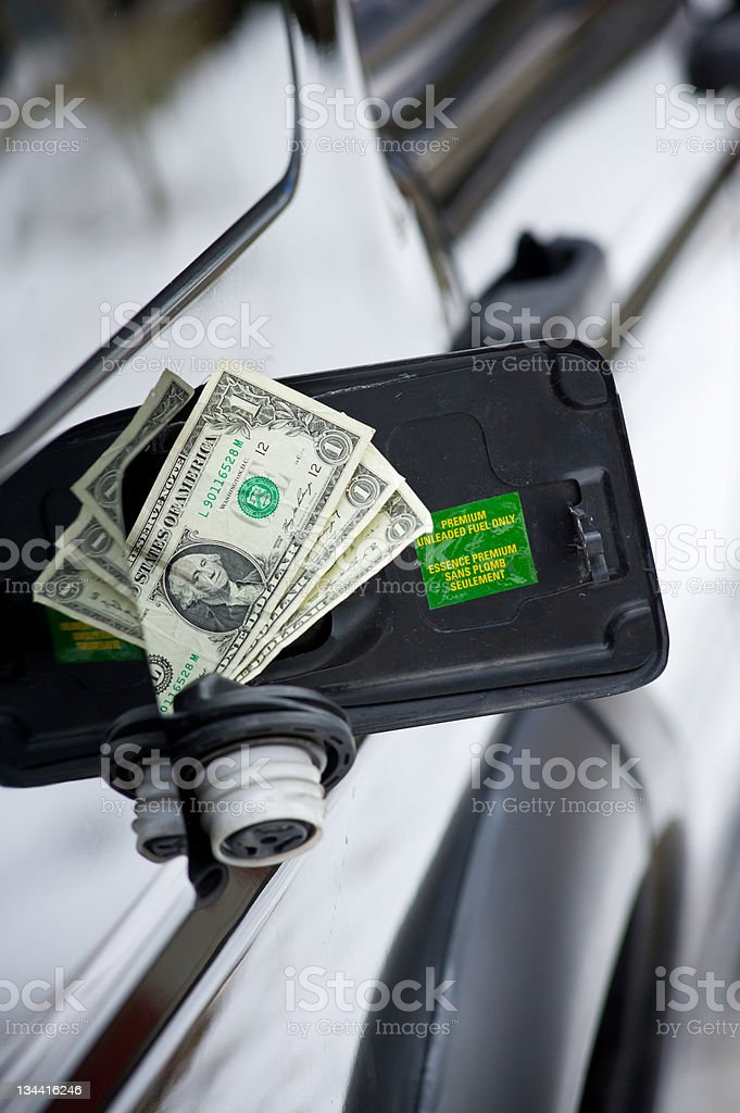 Money in Fuel Tank on SUV High Cost of Gasoline royalty-free stock photo