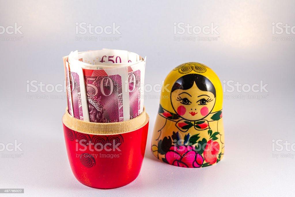 UK Money in Russia hands - £50 pound in Matryoshka stock photo