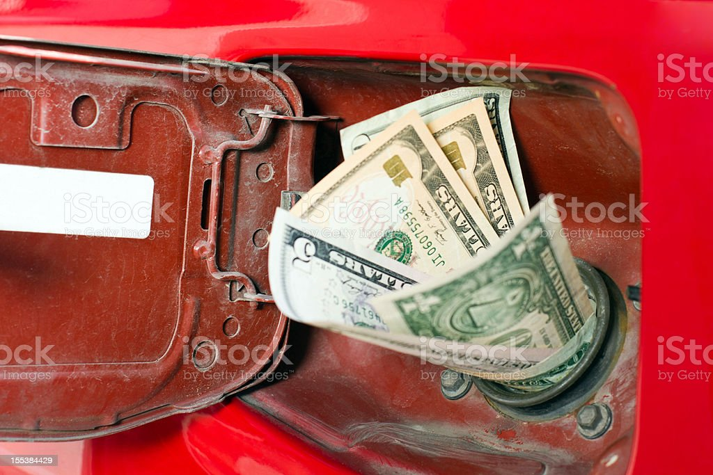 Money in the chute of a gas representing high gas prices stock photo