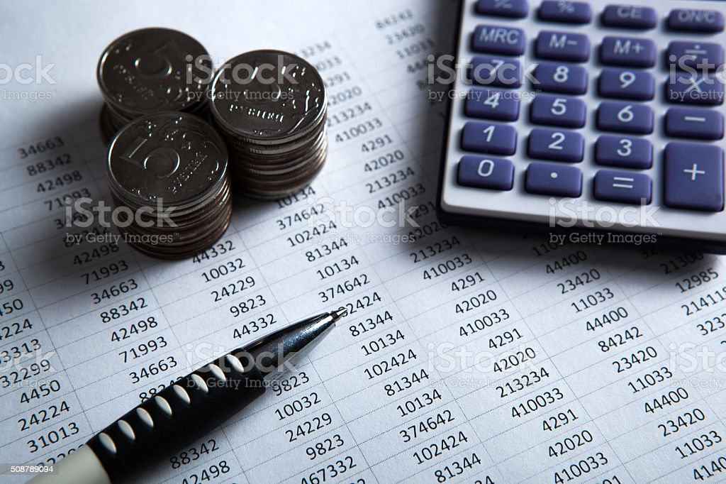 money in the form of banknotes and coins with calculator stock photo