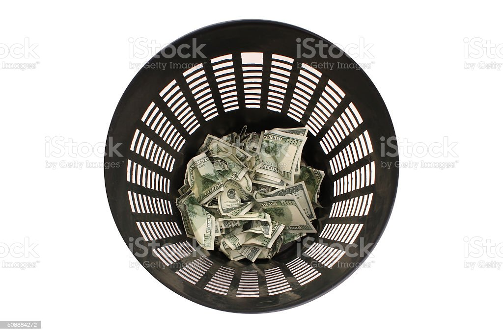 Money in the garbage trash bin stock photo