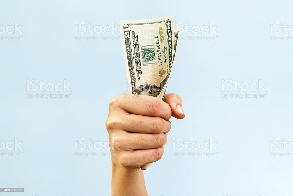 Money in the hand on blue background stock photo