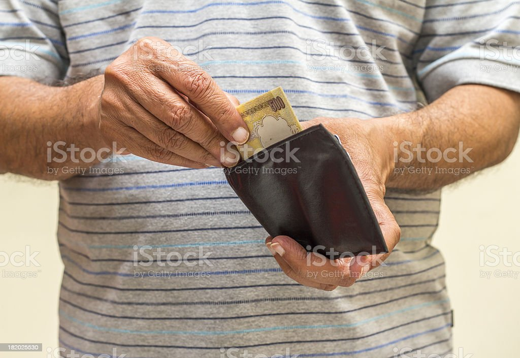 An adult Indian man takes out Indian rupees from his wallet