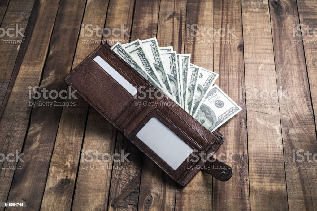Money in a leather wallet on wooden background. One hundred dollar...