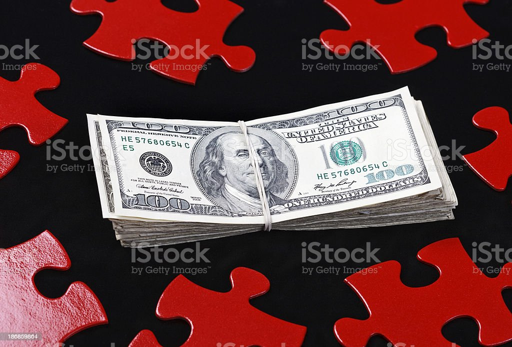 Money is puzzling; many dollars with red jigsaw pieces stock photo