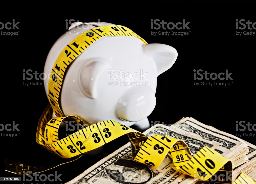 Money is tight! Piggybank wrapped in tape measure with dollars stock photo