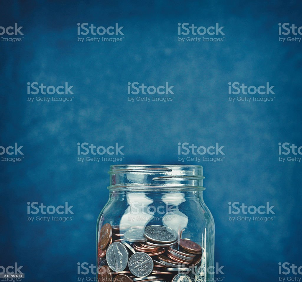Money jar half filled with American currency stock photo