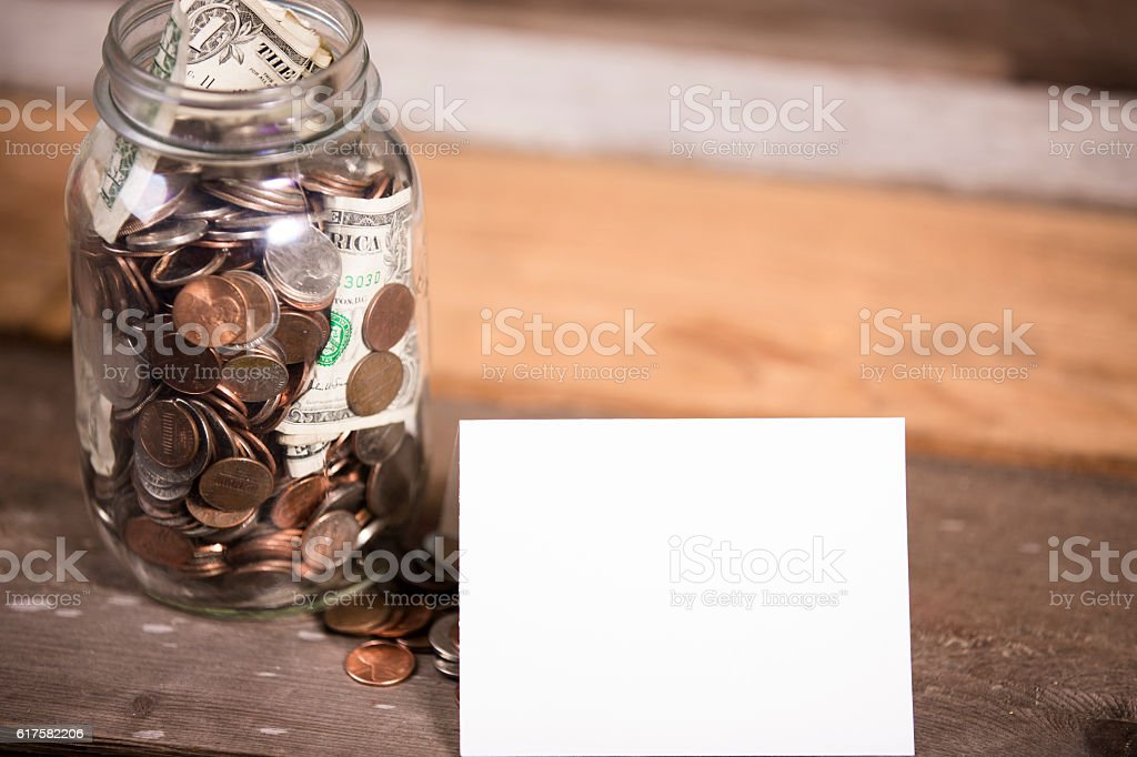 Money jar with U.S. currency represents savings, donations concepts. stock photo