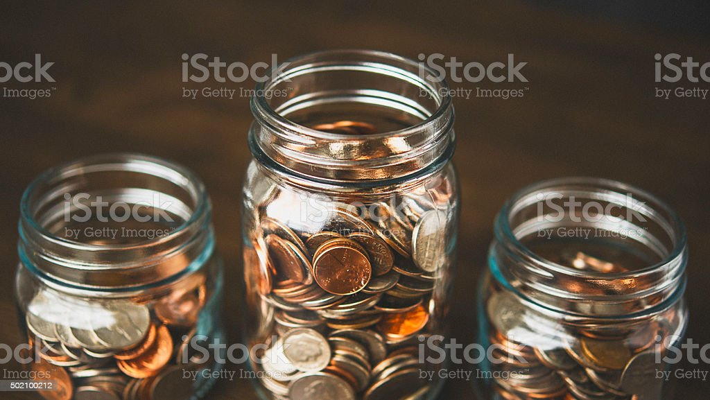 Money jars filled with American currency. Savings and donations concept. stock photo