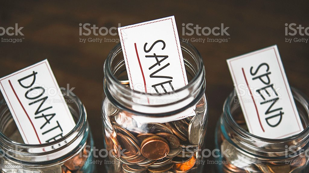 Money jars filled with American currency: Spend, save and donate stock photo