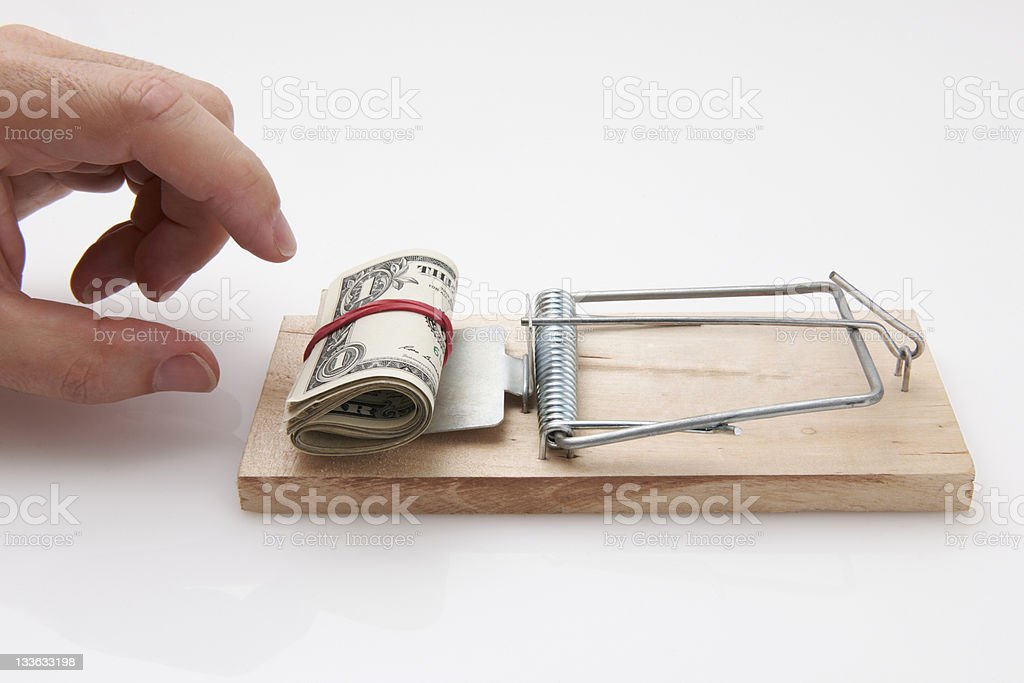 Money on a mousetrap with a hand trying to take it stock photo