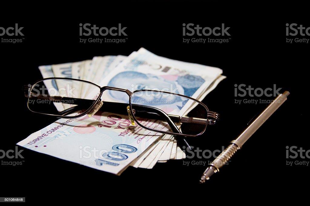 Money, pen and  glasses  on black background. stock photo