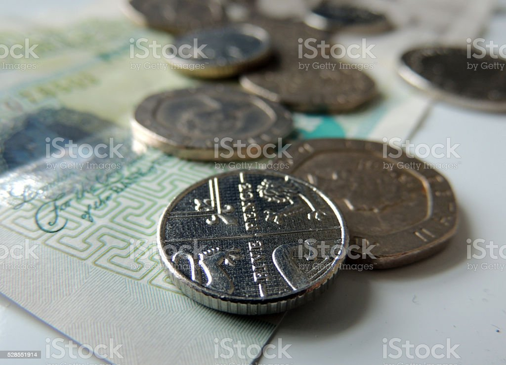 Money - pennies and pounds - focus on five pence coin stock photo