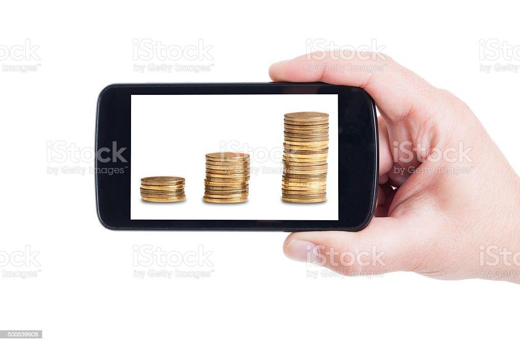 Money piles growing on smartphone screen stock photo