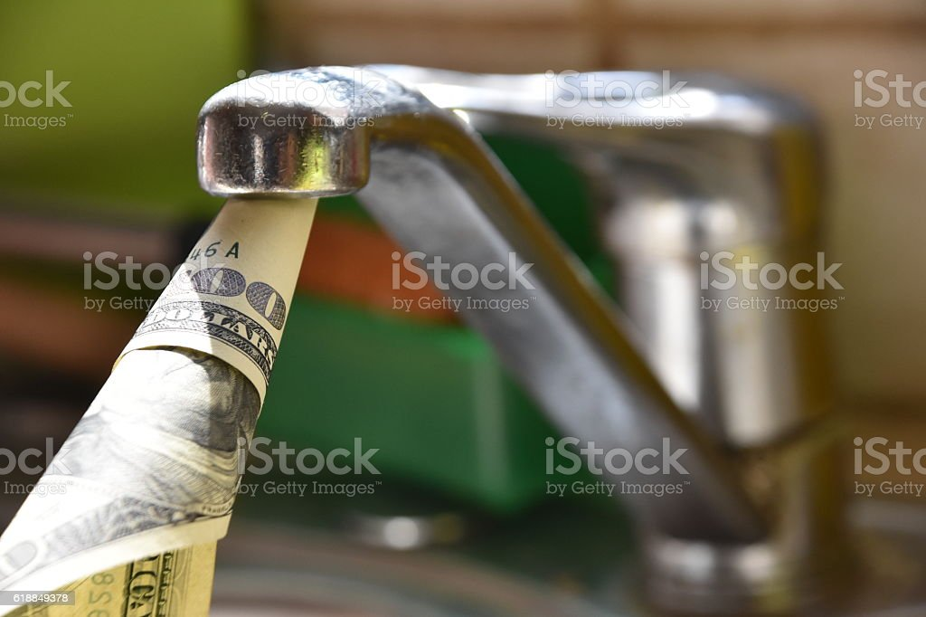 Money Pouring Out of Water Tap stock photo