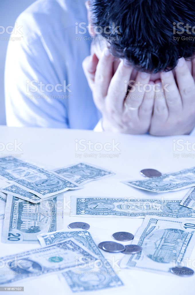 Money problems for man with dollar bills on a table royalty-free stock photo