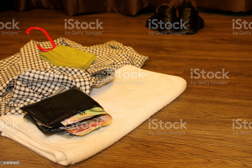 money purse and towel on wooden floor stock photo