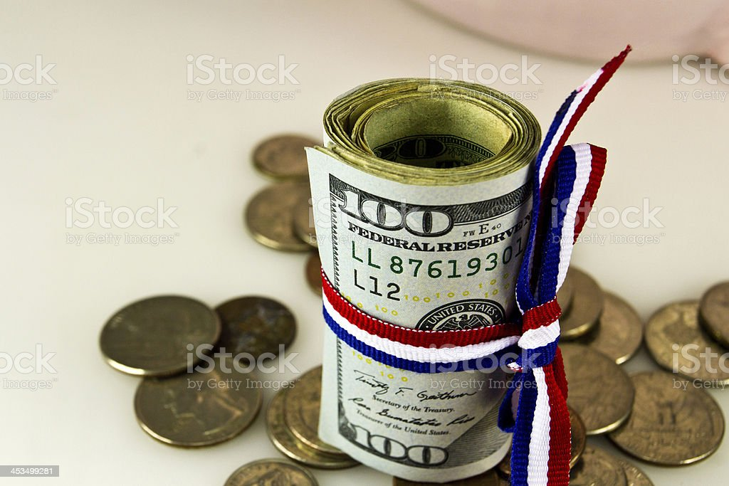 Money rolled up with new $100 dollar bill and coins stock photo