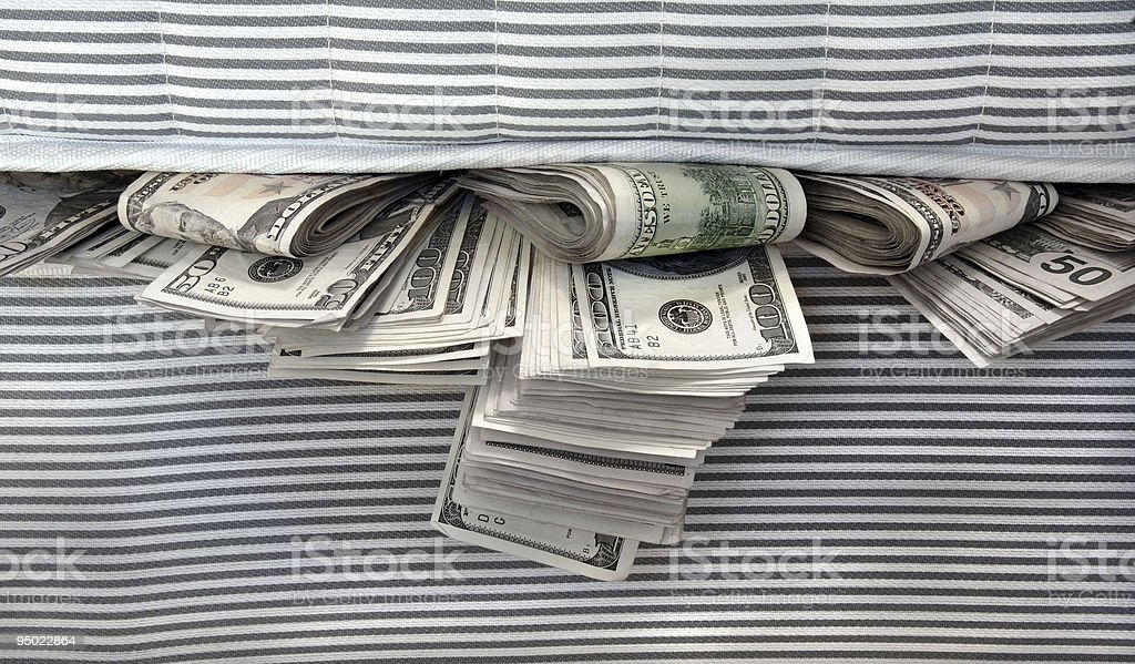 Money safely tucked in between striped mattresses stock photo