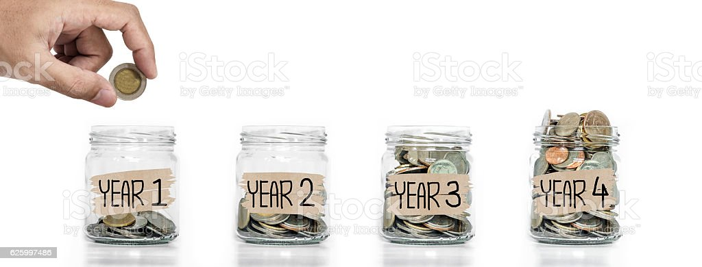 Money saving, Hand putting coin in glass jar stock photo