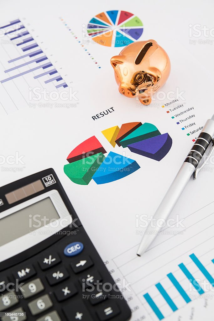 Money savings concept: charts, calculator, pen, pig royalty-free stock photo