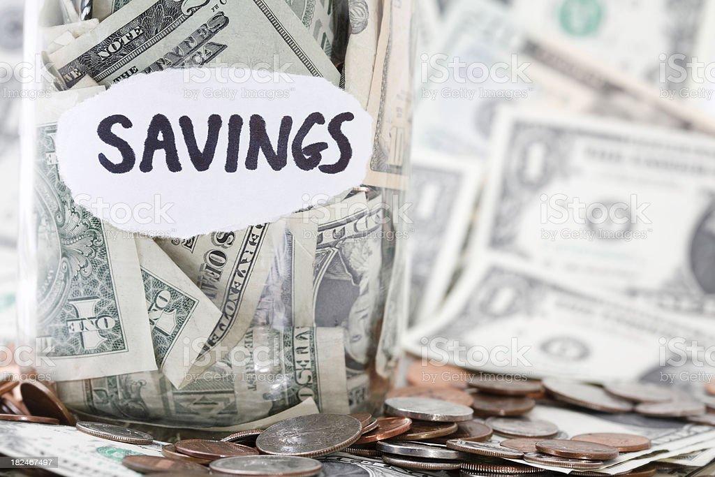 Money Savings Jar with U.S. Cash Around It stock photo